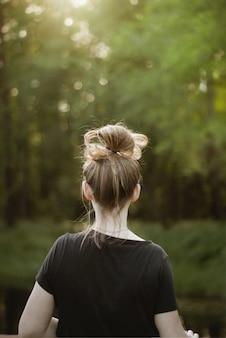 Foto vertical de uma jovem loira de camisa preta olhando para a bela vegetação