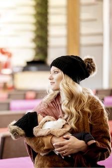 Foto vertical de uma jovem loira segurando seu bebê olhando para o lado