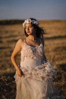 Foto vertical de uma jovem mulher branca com vestido branco e coroa de flores brancas posando em um campo