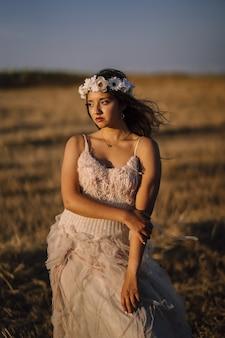 Foto vertical de uma jovem mulher branca com vestido branco e grinalda de flor branca posando em um campo