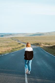 Foto vertical de uma jovem mulher de jeans andando na rodovia