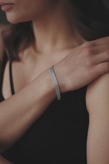 Foto vertical de uma jovem mulher usando uma linda pulseira de prata