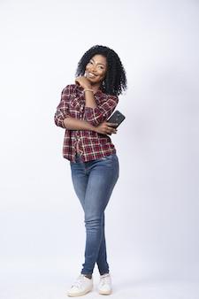 Foto vertical de uma jovem negra segurando o telefone sorrindo