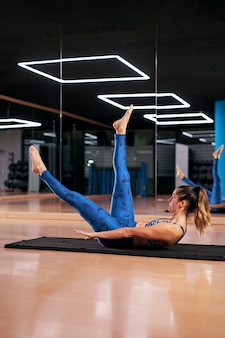 Foto vertical de uma jovem praticando ioga ou pilates em uma academia, se exercitando em uma roupa esportiva azul.
