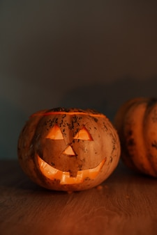 Foto vertical de uma lanterna de abóbora para o halloween na mesa em um quarto escuro