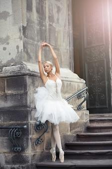 Foto vertical de uma linda bailarina dançando sensualmente ao ar livre na cidade, posando elegantemente na escada de um antigo castelo.