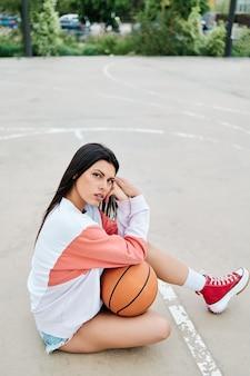 Foto vertical de uma linda jovem jogando basquete