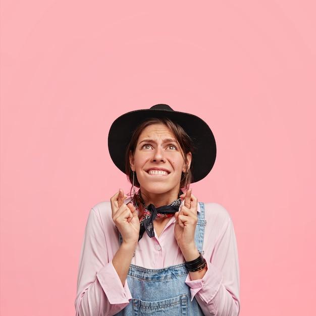 Foto vertical de uma linda jovem mulher com aparência desejável, morde os lábios, olha para cima com grande esperança enquanto mantém os dedos cruzados, usa chapéu preto e macacão jeans, fica de pé contra a parede rosa