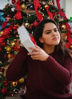 Foto vertical de uma linda jovem segurando um presente de natal