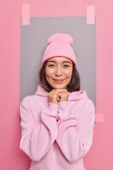 Foto vertical de uma linda mulher asiática com cabelo escuro mantém as mãos sob o queixo, sorri, usa boné e o capuz olha diretamente para as poses da câmera contra uma folha em branco colada na parede
