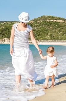 Foto vertical de uma mãe caucasiana caminhando na praia com a filha durante o dia