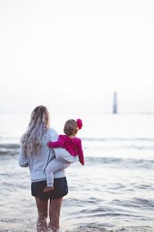 Foto vertical de uma mãe segurando seu bebê e olhando para o horizonte do mar