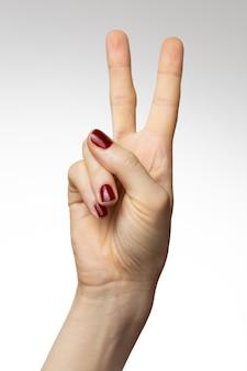 Foto vertical de uma mão feminina com um sinal da paz
