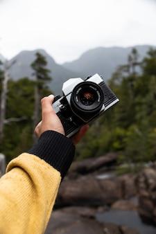 Foto vertical de uma mão masculina segurando uma câmera fotográfica profissional com uma floresta na