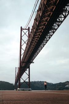 Foto vertical de uma menina correndo à beira do rio sob a ponte 25 de abril em lisboa, portugal