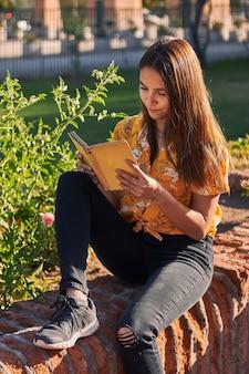Foto vertical de uma menina em uma camisa amarela lendo um livro sentada ao lado de plantas