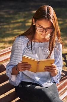Foto vertical de uma menina em uma camisa azul e óculos lendo um livro no banco