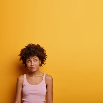 Foto vertical de uma menina milenar encaracolada pensativa olhando pensativamente para cima, vestida casualmente, vendo algo interessante ou atraente, isolada em uma parede amarela brilhante, tem expressão contemplativa