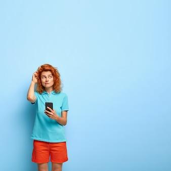 Foto vertical de uma menina ruiva pensativa coçando a cabeça e olhando com espanto