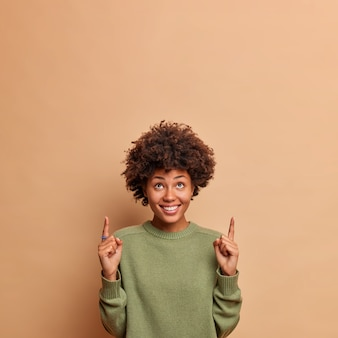 Foto vertical de uma modelo feminina feliz e alegre apontando para cima, com um sorriso largo, fica satisfeita em mostrar o espaço de cópia para seu conteúdo de publicidade e usa um macacão casual isolado na parede bege