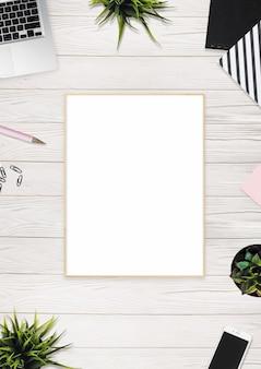 Foto vertical de uma moldura em branco, lápis e dispositivos de tecnologia na mesa