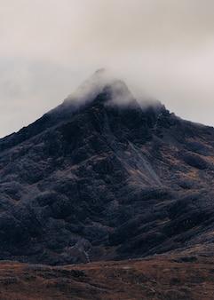 Foto vertical de uma montanha coberta por uma nuvem de névoa na escócia, ilha de skye