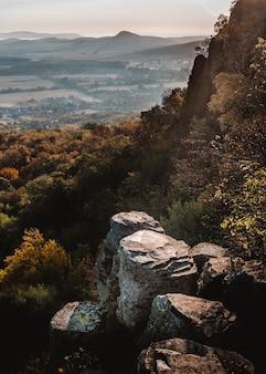 Foto vertical de uma montanha na hungria cheia de árvores e vegetação