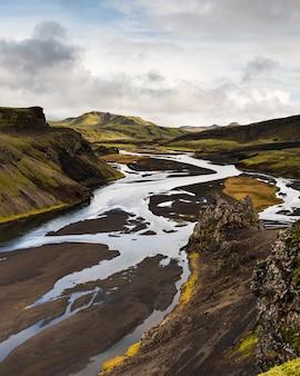 Foto vertical de uma montanha na região das terras altas da islândia com um céu nublado