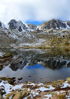 Foto vertical de uma montanha rochosa coberta de neve com um reflexo em um pequeno lago