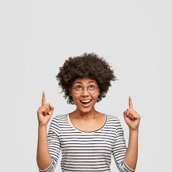 Foto vertical de uma mulher afro-americana de aparência agradável com expressão alegre, cabelo encaracolado, aponta para cima com os dedos indicadores