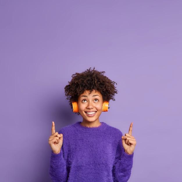 Foto vertical de uma mulher afro-americana feliz em um macacão casual indica acima, no espaço da cópia, tem uma expressão facial positiva, sorri de bom grado, usa fones de ouvido estéreo nas orelhas