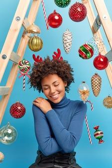 Foto vertical de uma mulher afro-americana satisfeita desfrutando de uma atmosfera mágica festiva em casa usando poses confortáveis de gola alta