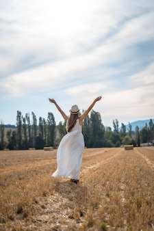 Foto vertical de uma mulher alegre em um vestido branco correndo por um campo sob a luz do sol