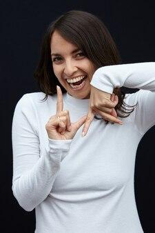 Foto vertical de uma mulher alegre mostrando los angeles com as mãos