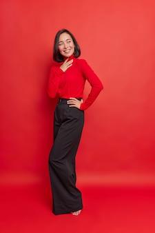 Foto vertical de uma mulher asiática bonita com cabelo escuro concentrado em risos e positivamente usa uma camisa elegante, vestidos de calça larga preta para eventos de férias isolados sobre uma parede vermelha vívida