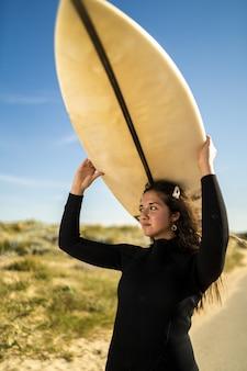 Foto vertical de uma mulher atraente carregando uma prancha de surf acima da cabeça