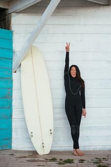 Foto vertical de uma mulher caucasiana vestindo um traje de surf com uma prancha de surf sorrindo alegremente