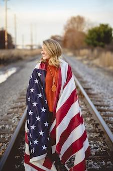 Foto vertical de uma mulher com a bandeira americana nos ombros, em pé na ferrovia
