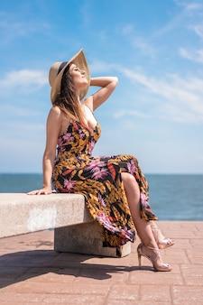 Foto vertical de uma mulher com um vestido de verão floral e um chapéu sentada à beira-mar, capturada na espanha