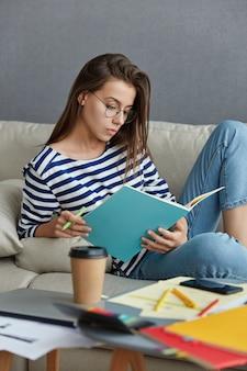 Foto vertical de uma mulher de aparência agradável carregando um caderno, posa em um sofá aconchegante interno