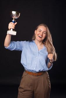Foto vertical de uma mulher de negócios segurando um troféu.