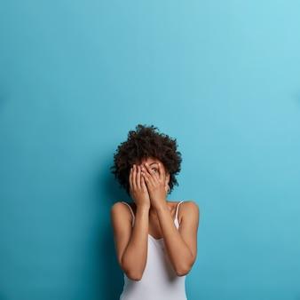 Foto vertical de uma mulher de pele escura assustada esconde o rosto, afasta algo, focado para cima, vê fobia, vestida com roupa casual, posa contra a parede azul, espaço livre para sua promoção