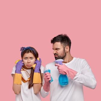 Foto vertical de uma mulher descontente tapa os ouvidos, não quer ouvir o marido zangado que reclama de muito trabalho doméstico, segura sprays, esponjas, faz limpeza de primavera, usa luvas de proteção, roupas brancas