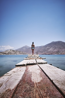 Foto vertical de uma mulher em pé na beira de um cais de madeira na ilha de amorgos, grécia