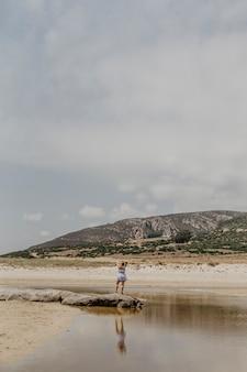 Foto vertical de uma mulher em pé na costa com montanhas ao fundo