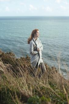 Foto vertical de uma mulher em pé na costa com o mar ao fundo