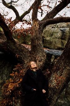 Foto vertical de uma mulher em pé perto de uma grande árvore, olhando para a câmera