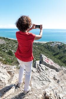 Foto vertical de uma mulher em pé sobre as rochas, fotografando o lindo mar