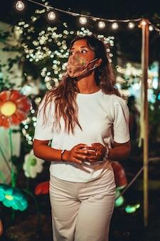 Foto vertical de uma mulher europeia bronzeada usando uma máscara floral em um parque de diversões Foto gratuita