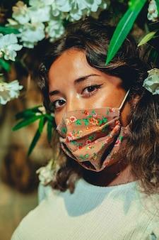 Foto vertical de uma mulher europeia bronzeada usando uma máscara floral em um parque de diversões